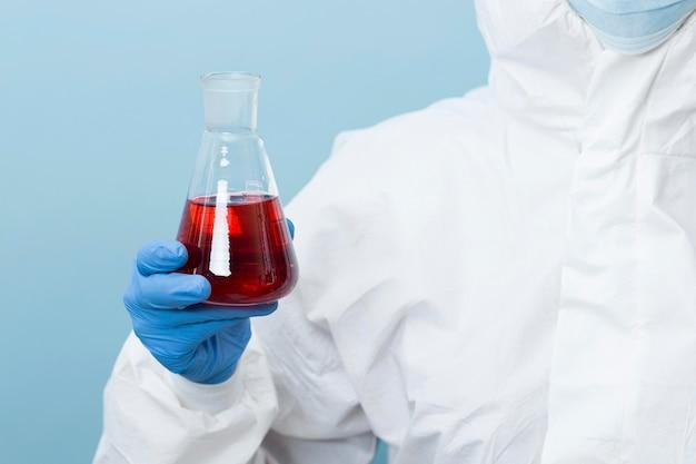 Vooraanzichtwetenschapper die een rood chemisch product houdt