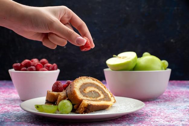 Vooraanzichtwijfje dat framboos neemt van plat ewith roll cake samen met appels en frambozen op donker