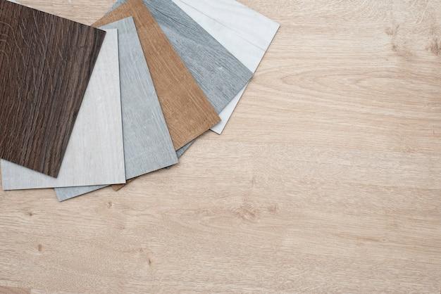 Voorbeeldcatalogus van luxe vinyl vloertegels met een nieuw interieurontwerp voor een huis of vloer op een licht houten tafel.