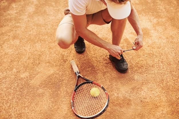 Voorbereiden. jonge tennisser in sportieve kleding is buiten op het veld.