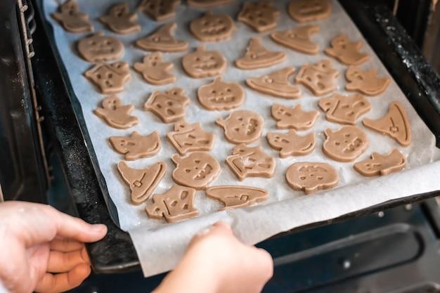 Voorbereiden om halloween te vieren en een traktatie voorbereiden. handen steken een bakplaat met rauwe halloween-koekjes in de oven. levensstijl