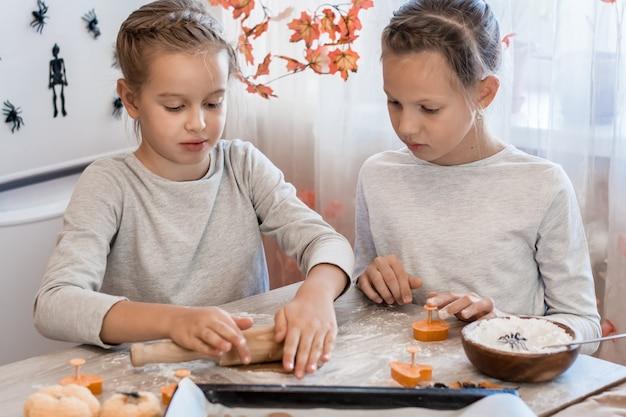 Voorbereiden om halloween te vieren en een traktatie voorbereiden. leuke meisjes rollen peperkoekdeeg uit voor het maken van halloween-koekjes op tafel. levensstijl