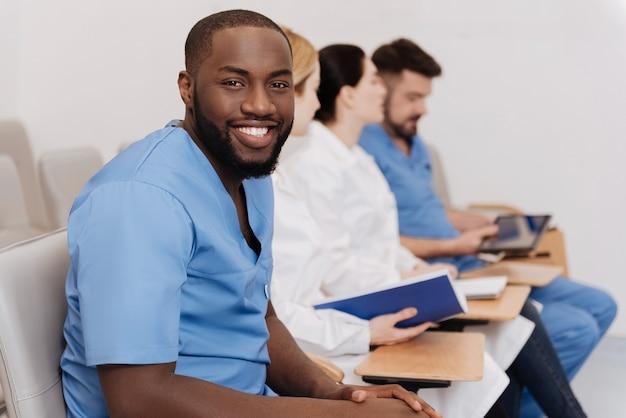Voorbereiden op toekomstig beroep. glimlachende ijverige optimistische stagiaires die de lezing in de medische universiteit bestuderen en beluisteren terwijl ze belangstelling tonen en aantekeningen maken