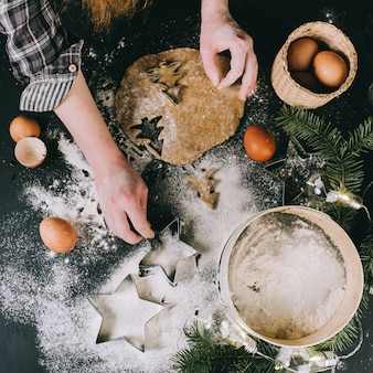 Voorbereidend kerstmiskoekje, hoogste mening, retro toegepaste filter, het concept van huiskerstmis op een grijze oppervlakte