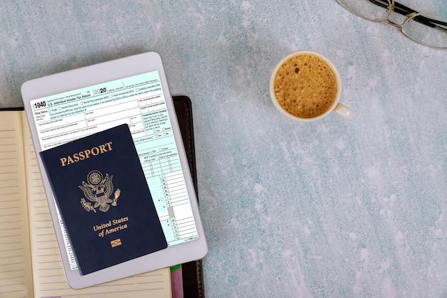 Voorbereiding aanvraag individuele inkomstenbelasting datum tijd aangifteformulier 1040 vs en amerikaans paspoort op koffiekopje