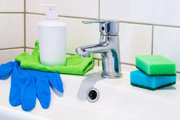 Voorbereiding om de wastafel in de badkamer te wassen met wasmiddelen. schoonmaakdienst. hulpmiddelen om netheid en hygiëne in de kamer te creëren