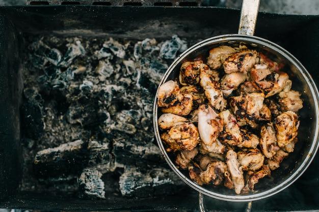 Voorbereiding op bbq. schotel met geroosterd vlees op abstracte achtergrond. warme smakelijke smokey barbecue maaltijd op kolen en verbrand brandhout. buiten koken. lekker ruikend eten. gebakken stukjes kip