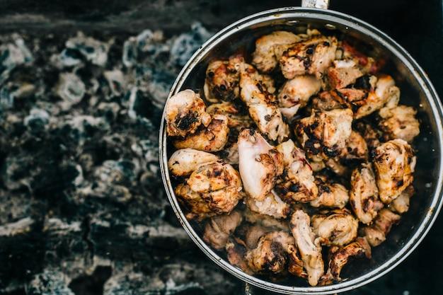 Voorbereiding op bbq. schotel met geroosterd vlees. warme smakelijke smokey barbecue maaltijd op kolen en verbrand brandhout.