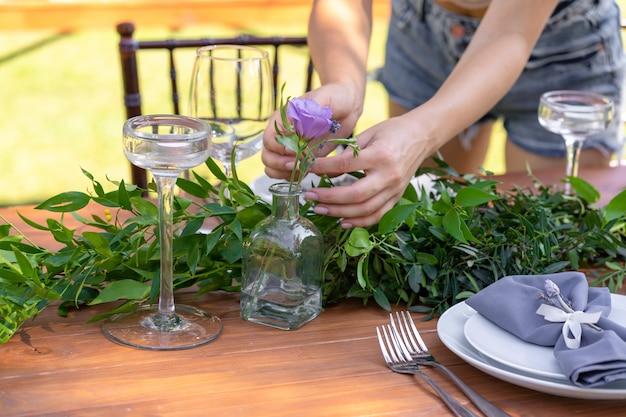 Voorbereiding op een openluchtfeest. meisje siert tafels met verse bloemen. decoratie details