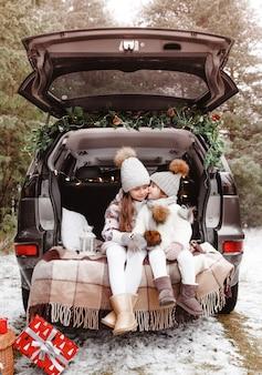 Voorbereiding op kerstmis. een klein meisje kust haar zus op de wang in de kofferbak van een auto