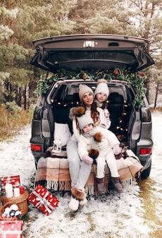 Voorbereiding op kerstmis. twee kleine meisjes spelen samen met hun moeder in de kofferbak van een auto