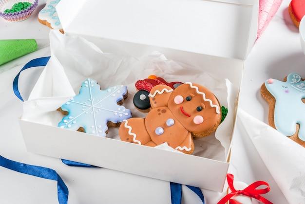 Voorbereiding op kerstmis, versieren van traditionele peperkoek met veelkleurige suikerglazuur, koekjes, peperkoek in een witte geschenkdoos, met strik op een witte marmeren tafel copyspace