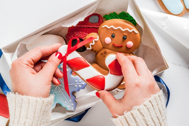 Voorbereiding op kerstmis, versieren van traditionele peperkoek met veelkleurige suikerglazuur, vouwt het meisje de koekjes in een witte geschenkdoos, met strik op een witte marmeren tafel copyspace bovenaanzicht