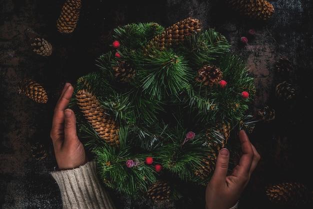 Voorbereiding op kerstvakantie. vrouw die kerstmis groene kroon verfraait met denneappels en rode de winterbessen
