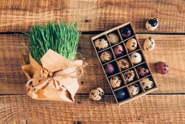 Voorbereiding op pasen. bovenaanzicht van graspakket en doos kwarteleitjes voor pasen liggend op houten rustieke tafel