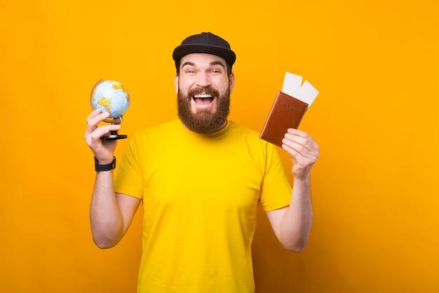 Voorbereiding op reis, vrolijk lachende bebaarde hipster man met paspoort met kaartjes en globe