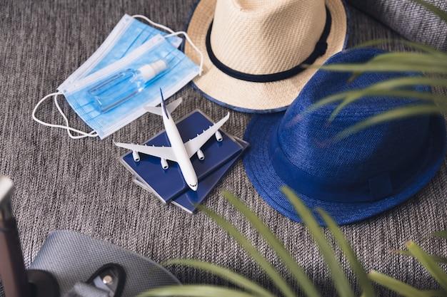Voorbereiding op reizen bij pandemie. paspoorten, hoeden, gezichtsmaskers en handdesinfecterend middel. vluchtregels tijdens coronavirus-pandemie.