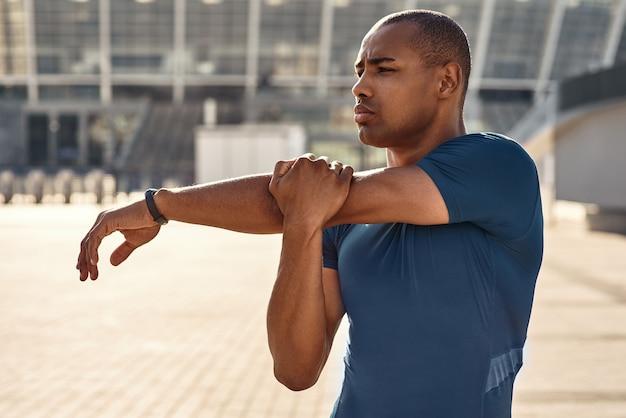 Voorbereiding op training close-up portret van afrikaanse atleet die zijn armen uitstrekt tijdens de ochtend