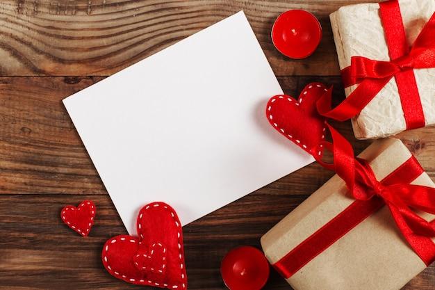 Voorbereiding op valentijnsdag. rode harten en ambachtelijke geschenken op hout. kopieer ruimte