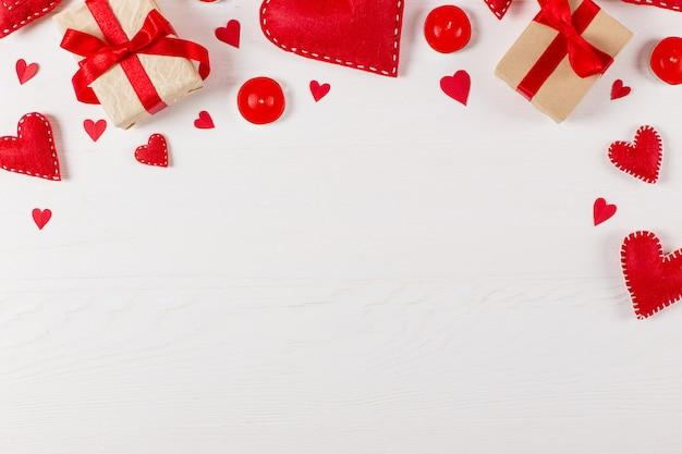 Voorbereiding op valentijnsdag. rode harten en ambachtelijke geschenken op wit hout. kopieer ruimte