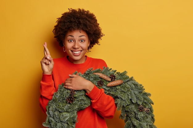 Voorbereiding op wintervakantie en feestelijk interieur. vrolijke afro-amerikaanse vrouw kruist vingers, maakt wens, vormt met de kroon van kerstmis