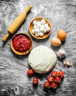 Voorbereiding pizza. deeg met saus, mozzarella en tomaten. op rustieke ondergrond