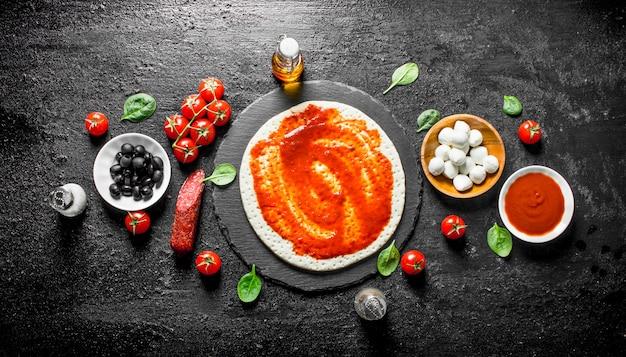 Voorbereiding pizza. deeg met verschillende ingrediënten voor het koken van pizza. op zwarte rustieke ondergrond
