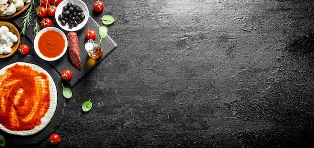 Voorbereiding pizza. deeg met verschillende ingrediënten voor het koken van pizza op zwarte rustieke tafel