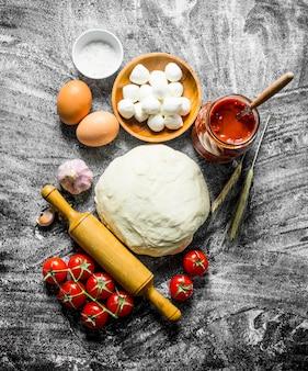 Voorbereiding pizza. diverse ingrediënten voor het koken van pizza op rustieke tafel