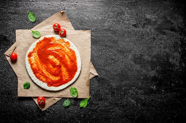 Voorbereiding pizza. uitgerold deeg met tomatenpuree. op zwarte rustieke achtergrond