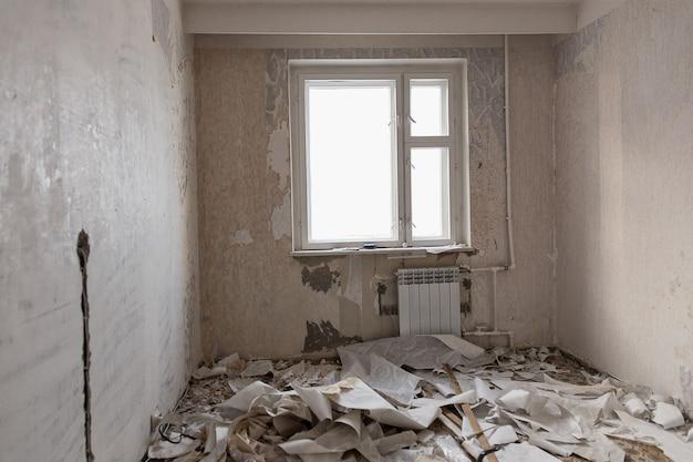 Voorbereiding van de kamer voor reparatie. muren van behang in appartement schoonmaken.