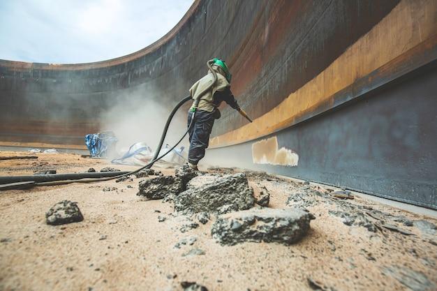 Voorbereiding van de oppervlaktecorrosieplaat van de vrouwelijke werknemer door zandstralen van de interne olie van de tank