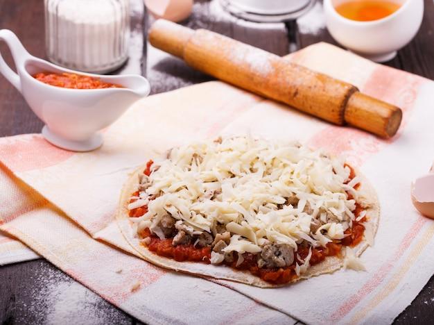 Voorbereiding van de pizza, omringd door ingrediënten.