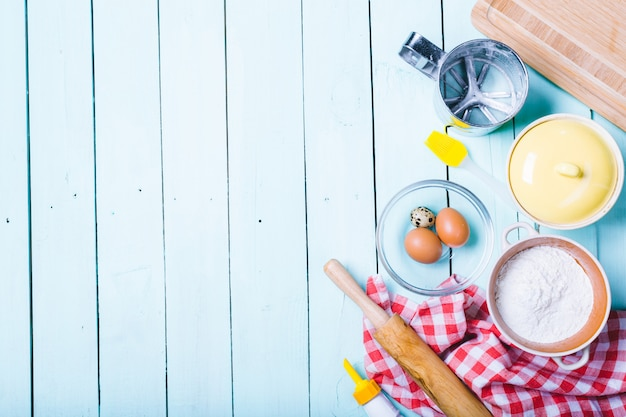 Voorbereiding van het deeg. ingrediënten voor het deeg - eieren en bloem met een deegroller. op houten achtergrond.