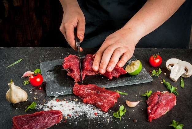 Voorbereiding van het diner. koken, verwerken van vlees (rundvlees, ossenhaas). persoon (vrouwelijke handen) snijdt een stuk vlees in steaks (stukken). zwarte betonnen tafel, specerijen en kruiden in het frame.