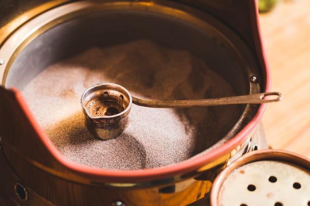 Voorbereiding van turkse koffie in cezve op zand bij koffiestaaf
