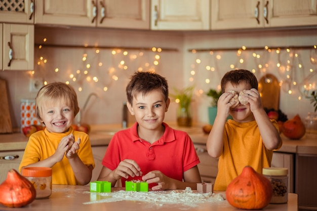 Voorbereiding voor de vakantie halloween. drie vrolijke kinderen maken koekjes in de keuken