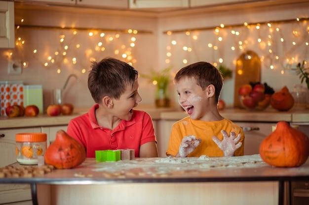 Voorbereiding voor de vakantie halloween. twee vrolijke kinderen maken koekjes in de keuken