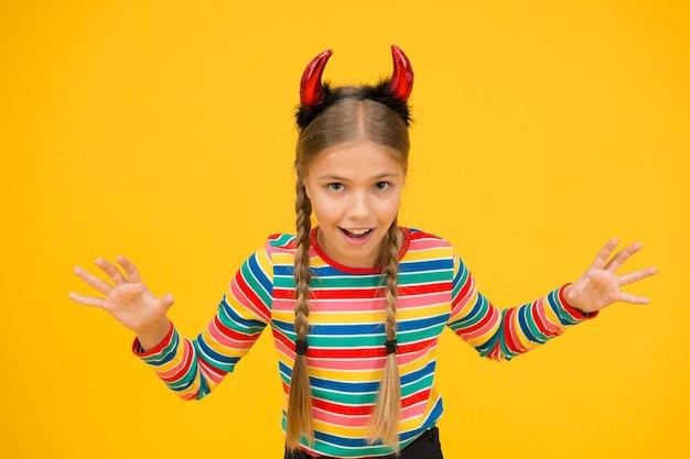Voorbereiding voor feest. kleine demon. speels demonenmeisje. kleine demon binnen. meisjesachtig humeur. leuk maar gevaarlijk. halloween-concept. klein schattig kind met rode hoorns. accessoires voor carnaval.