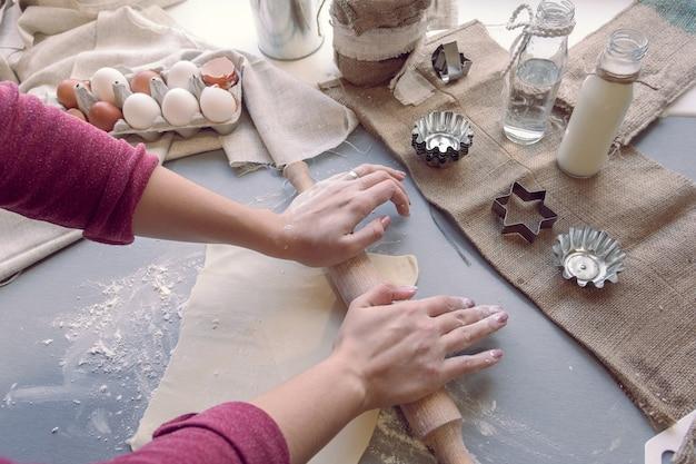 Voorbereiding voor het bakken van koekjes: vrouwenhanden rollen het deeg uit