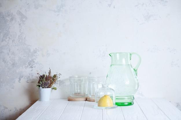 Voorbereiding voor het koken van limonade. fris, zomer verfrissend drankje. karaf met water, glas en citroen op witte cocncrete achtergrond. minimalisme met kopie ruimte. limonade maken. ingrediënten om te maken
