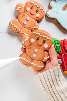 Voorbereiding voor kerstmis het meisje (handen op de foto) siert zelfgemaakte handgemaakte traditionele peperkoek met veelkleurige suiker glazuur koekjes wit marmeren tafel