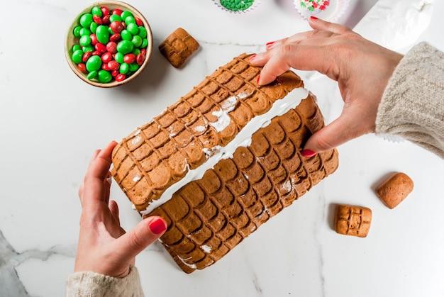 Voorbereiding voor kerstmis, nieuwjaar. koken en decoratie van traditionele komst peperkoek huis, vrouwelijke handen in beeld, bovenaanzicht, wit marmer.