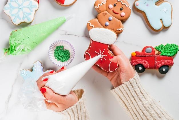 Voorbereiding voor kerstmis, siert het meisje zelfgemaakte peperkoek