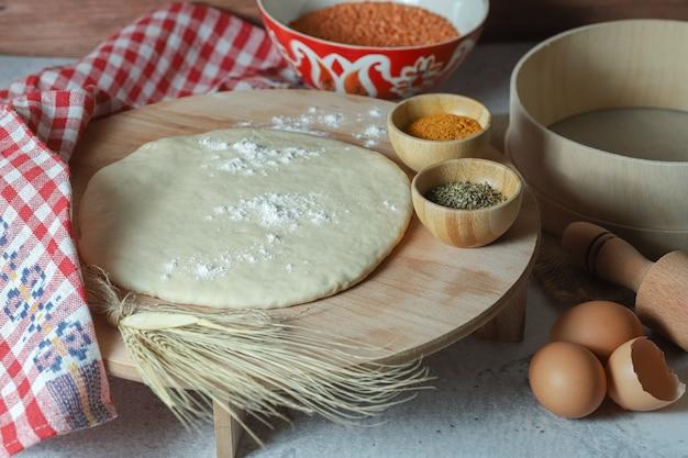 Voorbereidingen voor pizzadeeg met veel producten.