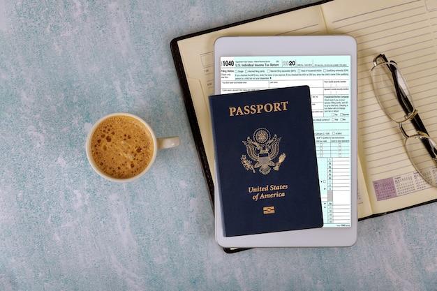 Voorbereidingsaanvraag 1040 amerikaanse individuele inkomstenbelasting en amerikaans paspoort met bril in de e-form digitale tablet