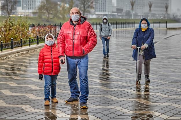 Voorbijgangers aan de oever van de rivier bij koud bewolkt weer zijn gekleed in warme kleren en dragen beschermende medische maskers op hun gezicht.