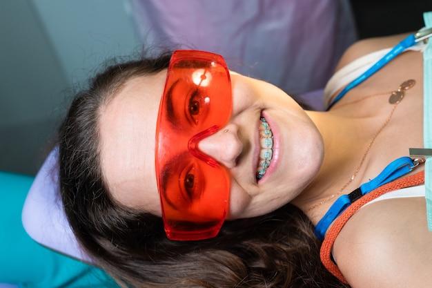 Voordat u begint met het verwijderen van beugels van een blank meisje in een tandheelkundige kliniek met een vrouwelijke tandarts