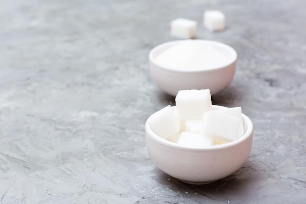 Voordelen van geraffineerde suiker boven kristalsuiker. twee soorten suiker in witte kommen op tafel, naast elkaar staan