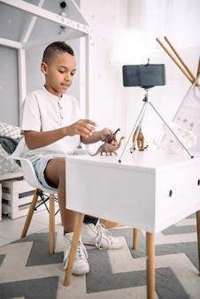 Voordelen van visualisatie. enthousiaste afro-amerikaanse jongensblogger die met speelgoed van dinosaurussen speelt tijdens het opnemen van video